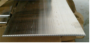 Sample of a mini-channel strip. Water or heat transfer fluid would pass through the channels seen on the edge of this strip.